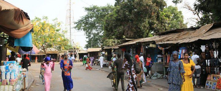 De grote markt in de West-Gambiaanse stad Brikama, waar je terecht kunt voor fruit, flatscreens, stoffen en smartphones , is 's avonds een gezellige chaos.